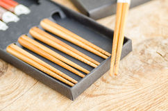 Chinese bamboo chopsticks in black box on wooden background Royalty Free Stock Photo