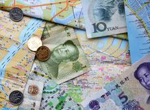 Chinese bank notes and coins on a Chinese maps Stock Photography