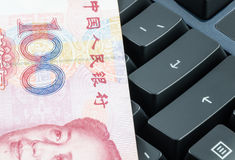 Chinese banknote on the computer keyboard Royalty Free Stock Photo