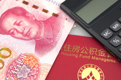 Chinese banknotes,calculator and housing accumulation fund bankbook on white background. Black calculator and hundred chinese banknotes with bankbook on white Royalty Free Stock Photo