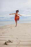 Chinese beauty. Is running with colorful one piece dress on the beach Royalty Free Stock Photo