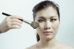 Chinese beauty applying makeup with brush Royalty Free Stock Photos