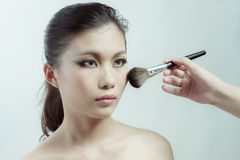 Chinese beauty applying makeup with brush Royalty Free Stock Image
