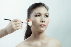 Chinese beauty applying makeup with brush Royalty Free Stock Photo