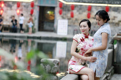 Chinese beauty girlfriends in cheongsam enjoy free time Royalty Free Stock Image