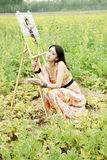 Chinese beauty outdoor. Chinese beauty with her oil painting in rape field Stock Photography