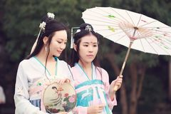 Cosplay Chinese classic beauty bestie best close friends in traditional ancient drama costume hanfu. Chinese beauty in traditional ancient costume, hold a fan on stock images