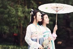 Cosplay Chinese best close friends bestie in traditional ancient drama costume hanfu. Chinese beauty in traditional ancient costume, hold a fan on hand, elegant stock photos