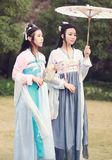 Cosplay Chinese best close friends bestie in traditional ancient drama costume hanfu. Chinese beauty in traditional ancient costume, hold a fan on hand, elegant Royalty Free Stock Images