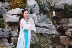 Chinese classic beauty in traditional ancient drama costume stand by rockery Stock Photo