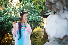 Chinese beauty in traditional ancient drama costume play flute Stock Photos