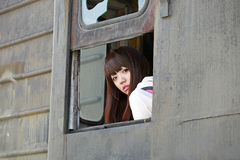 Chinese beauty on train. Chinese girl sitting on an old train caboose Royalty Free Stock Image