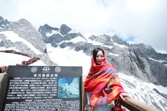 Chinese beauty wears red bandanna tour Jade dragon snow mountain. Chinese girl climb Jade dragon snow mountain at Yunnan province, it is a very famous snow stock images