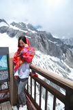 Chinese beauty wears red bandanna tour Jade dragon snow mountain. Chinese girl climb Jade dragon snow mountain at Yunnan province, it is a very famous snow stock photo