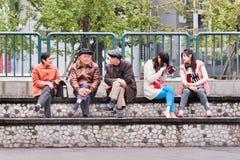 Chinese bejaarden en kereltjes samen voor een praatje, Chongqing, China Stock Afbeelding