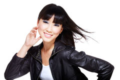 Chinese biker chick in black with windswept hair. Hot, sexy, Chinese biker chick dressed in black leather jacket and striking a cute pose with windswept hair Royalty Free Stock Photos