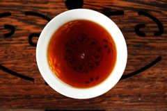 Chinese black puerh tea in white bowl on wooden tea tray Stock Images