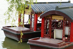 Chinese boats. Traditional chines boats with roofs floating on a lake by willow branches Stock Photography