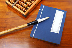 Chinese book and abacus. On the wooden table Stock Photos