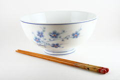 Rice bowl and chopsticks. Traditional Chinese rice bowl with pair of chopsticks, white studio background royalty free stock photo