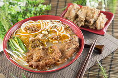 Chinese bowl of noodle with fried pork ribs and herbs on the tab Royalty Free Stock Image