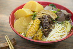 Chinese bowl of noodle with squid, dried pig blood and radish on Royalty Free Stock Photo