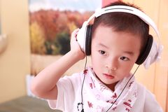A Chinese boy in cool dress is listening music by headset Stock Images