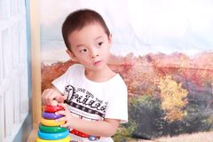 A Chinese boy in cool dress is playing his toys Stock Images
