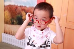 A Chinese boy in cool dress is wearing a red toy glasses Royalty Free Stock Photography