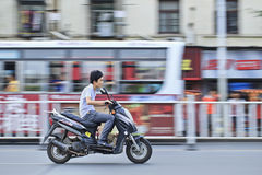 Chinese Boy with dog on gas motorcycle. XIANG YANG-CHINA-JULY 1. Boy with a dog on a gas motorcycle. Demand for gas motorcycles in China increases mainly in Stock Photography