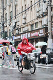Chinese boy dressed in rainwear on an e-bike, Shanghai, china Royalty Free Stock Photography