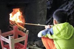Chinese boy learn to light fire Stock Image