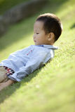 Chinese boy lying on the grass Stock Photo