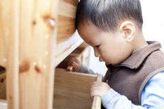 Chinese boy openning a wodden drawer. Asian chinese boy openning a  drawer Stock Image