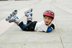 Chinese boy playing skate. Sitting on the ground Royalty Free Stock Images