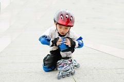 Chinese boy playing skate. Sitting on the ground Stock Images