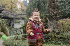 Chinese boy wield toy. Chinese happy boy wielding toy in park Stock Photo