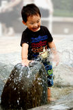 Chinese boy playing with water. A cute chinese boy playing with water and laughing cheerfully Royalty Free Stock Photography