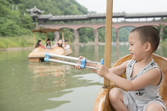 Chinese boy playing water gun Royalty Free Stock Photo