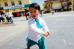 Chinese boy on the street in school uniform. Happy chinese kid join out door activity on the street stock photography
