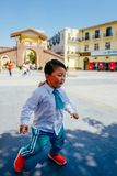 Chinese boy on the street in school uniform. Happy chinese kid join out door activity on the street royalty free stock images