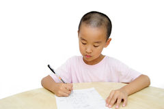 Chinese boy writing at table Royalty Free Stock Photography