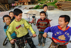 Chinese boys riding bikes on the ethnic village peoples. Stock Photos