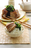Chinese braise pork belly. Braise pork belly slice over a bowl of rice and sauteed vegetable Royalty Free Stock Image