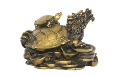 Chinese Brass Tortoise Lucky Charm. Chinese brass lucky charm of a tortoise resting on coins and with a smaller tortoise resting on top of it Stock Photos