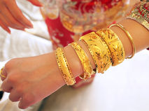 Chinese bride. Traditional Chinese bride wears a lot of gold bangles on wedding day Royalty Free Stock Image