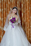 Chinese bride. Wearing a wedding dress, wearing a headdress, holding flowers, wedding onto the red carpet Stock Photos