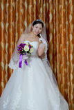 Chinese bride. Wearing a wedding dress, wearing a headdress, holding flowers, wedding onto the red carpet Stock Photo