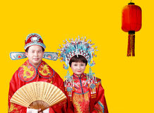 Chinese bride and groom. In traditional dress on yellow Stock Image