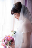 A chinese Bride looking at bouquet Stock Images